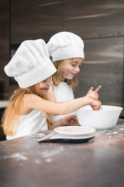 汚れたキッチンカウンターの上にボウルに食べ物を準備する2つの幸せな兄弟 無料写真
