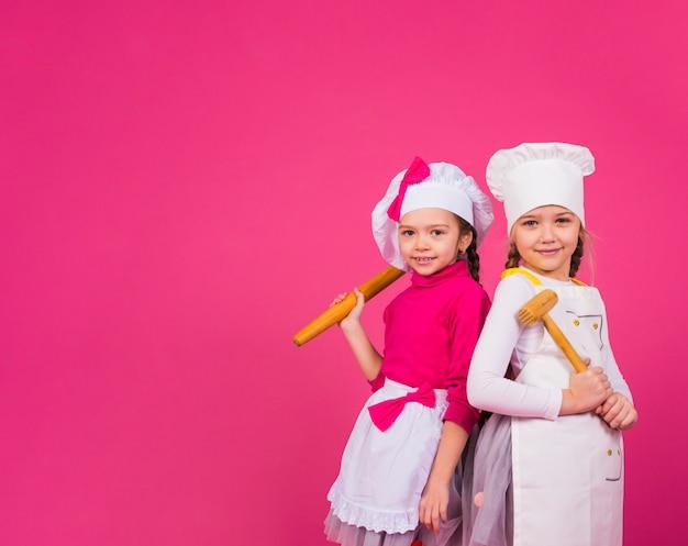 2人の女の子が台所用品と一緒に立って調理します 無料写真