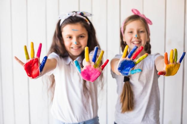 カラフルなペンキの手を示す2人の笑顔の女の子の選択と集中 無料写真