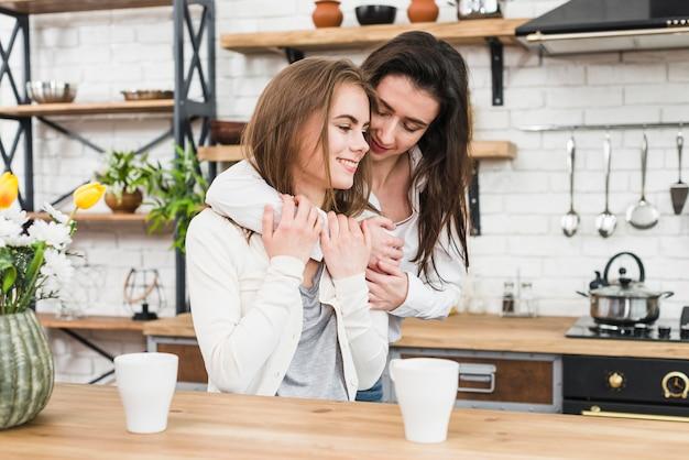 2つのコーヒーカップと木製のテーブルの前でロマンチックな若いカップル 無料写真