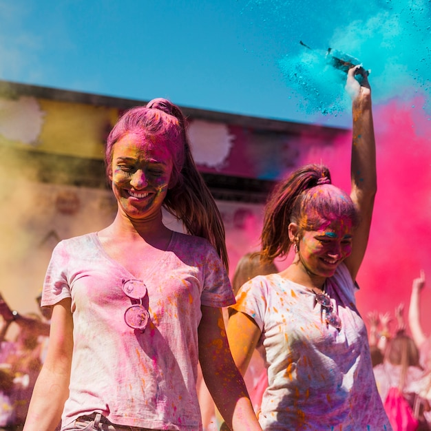 ホーリー祭で踊るホーリーカラーで覆われた2人の若い女性 無料写真