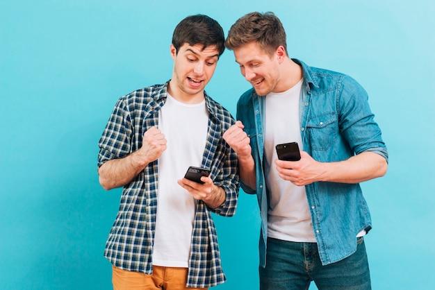 青い背景に携帯電話を見て彼らの拳を噛みしめる2人の男性の友人 無料写真