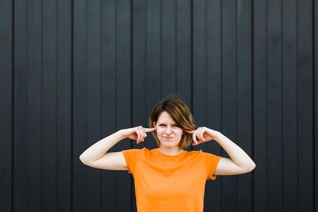 2本の指で彼女の耳を閉じる黒い壁に立っている若い女性のクローズアップ 無料写真