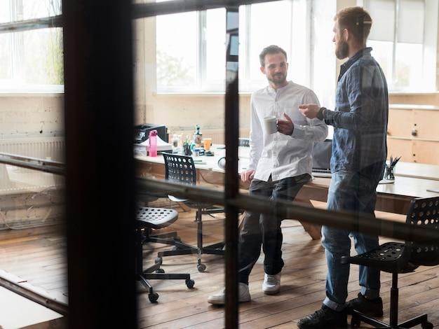職場で話している2つの男性実業家 無料写真