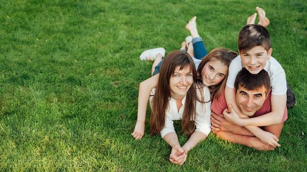 両親と公園の芝生の上に横たわる2人の素敵な子供たち 無料写真