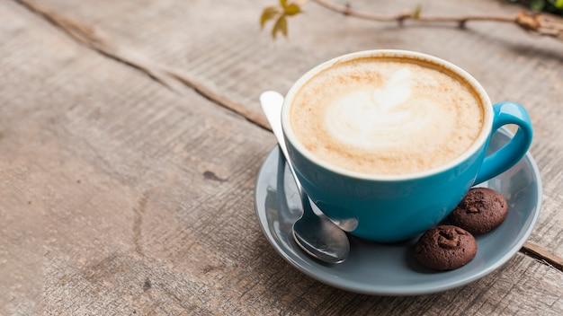 木製の机の上の2つの焼きクッキーと創造的なカフェラテアートコーヒーカップ 無料写真