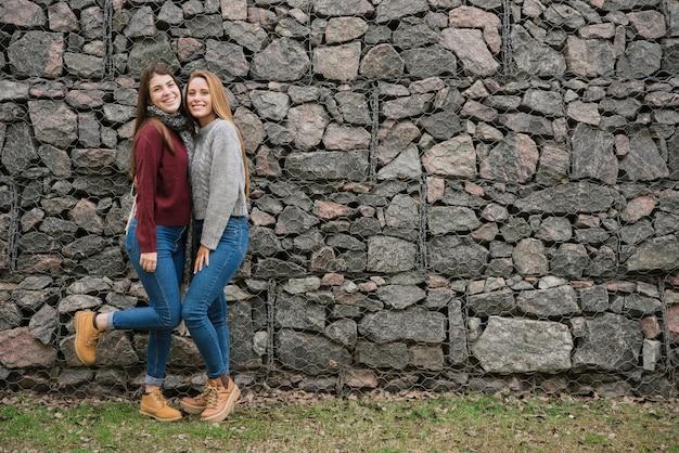 石の壁の前で2人の笑顔若い女性 無料写真