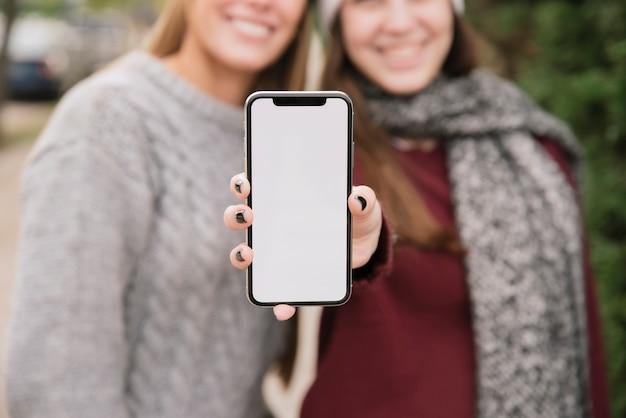 手で携帯電話を保持している2人の笑顔の女性を閉じる 無料写真
