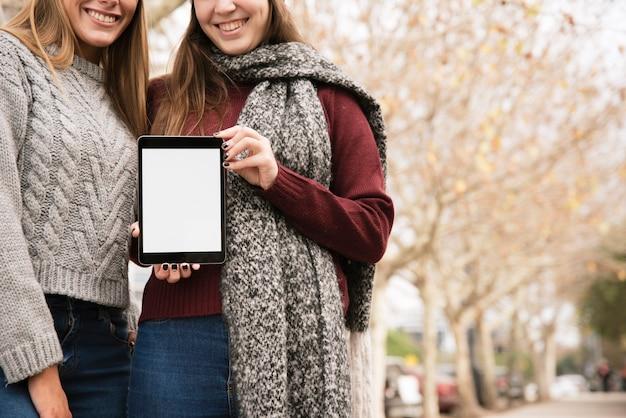 手でタブレットを保持している2つのエレガントな女性を閉じる 無料写真