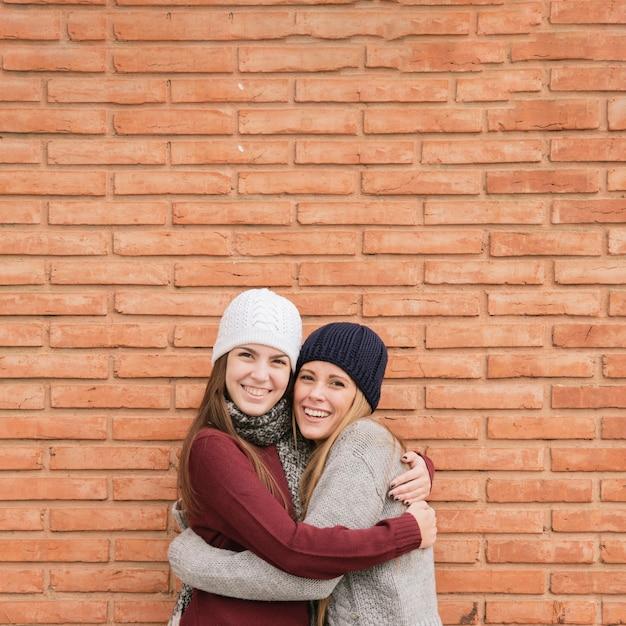 レンガの壁の前で肖像画2ハグする若い女性を閉じる 無料写真