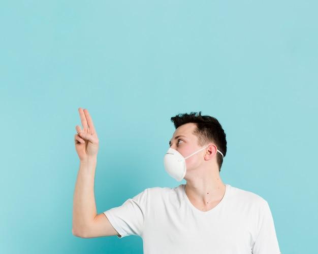 医療マスクと2本の指を指している男の側面図 無料写真