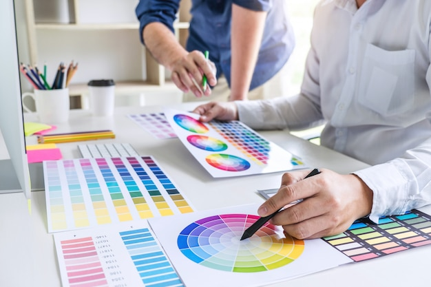 色の選択と色見本に取り組んでいる2人の同僚のグラフィックデザイナー Premium写真