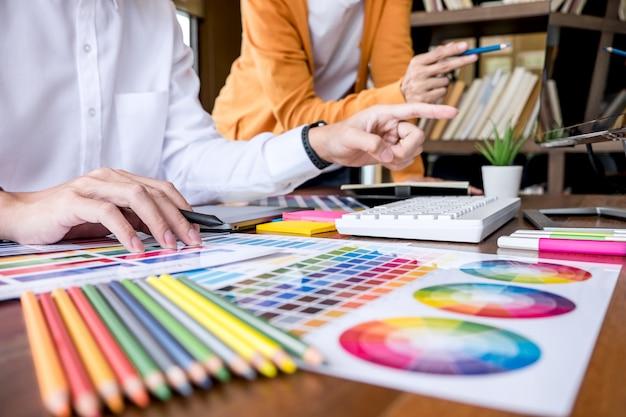 色の選択とグラフィックタブレットでの描画に取り組んでいる2つの創造的なグラフィックデザイナー Premium写真