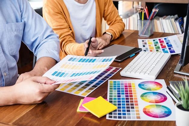 2人の同僚のカラー選択とグラフィックタブレットでの描画に取り組んでいる創造的なグラフィックデザイナー Premium写真