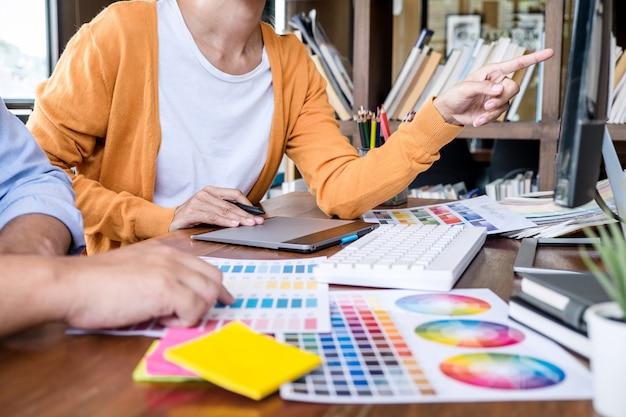 色の選択と色見本に取り組んで、グラフィックタブレットに描く2つの創造的なグラフィックデザイナー Premium写真