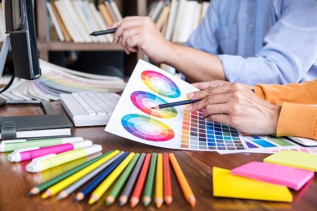 2人の同僚の色選択に取り組んでいると職場でグラフィックタブレットに描く創造的なグラフィックデザイナー Premium写真
