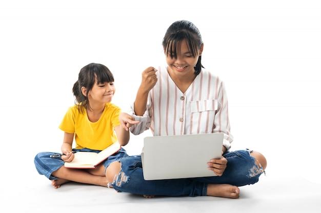 座っている2人の若いアジアの女の子と白い背景で隔離のラップトップを使用 Premium写真