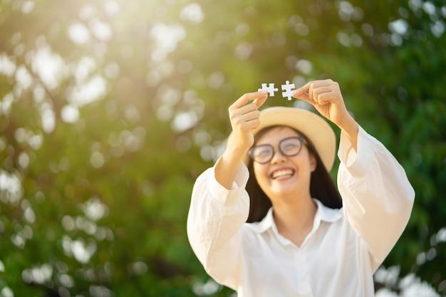 2つのジグソーパズルを示す幸せな女の子。愛の完了。 Premium写真