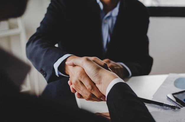 会社のオフィスの会議室でビジネス署名契約後に握手する2つのビジネス人々 Premium写真