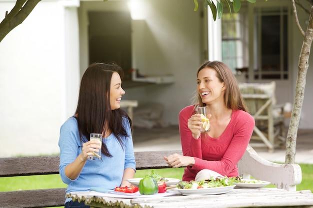 外に座って昼食を取る2人のガールフレンド Premium写真