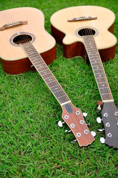 明るい緑の草のテクスチャに2つのギター Premium写真