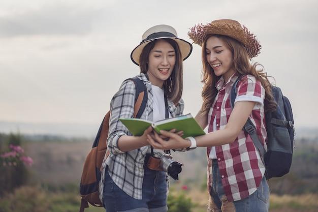 旅行中にロケーションマップ上の方向を検索する2人の女性 Premium写真