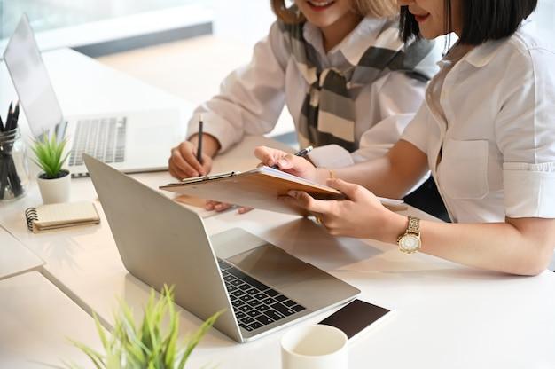 作業テーブルのスタートアップビジネスプロジェクトと会議2つの若い女性。 Premium写真