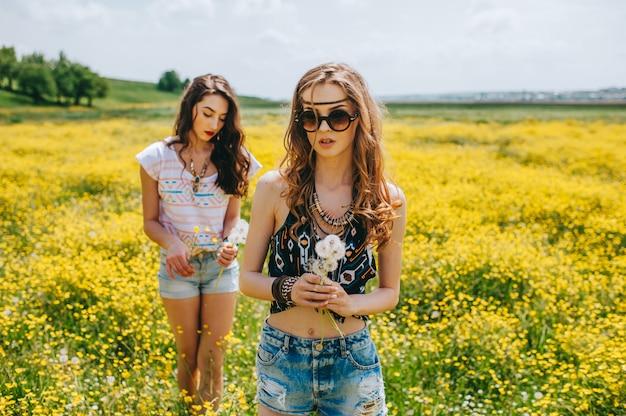 黄色の花の分野で2美しいヒッピーの女の子 Premium写真