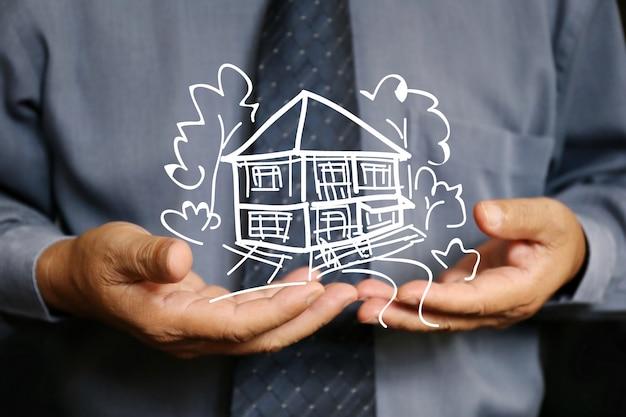 ビジネスマンは2つの手を保持する家を使用します。 Premium写真