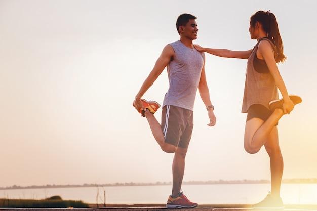 2つの若いカップルの夕日を背景に野外練習のためにワームアップ選手 Premium写真