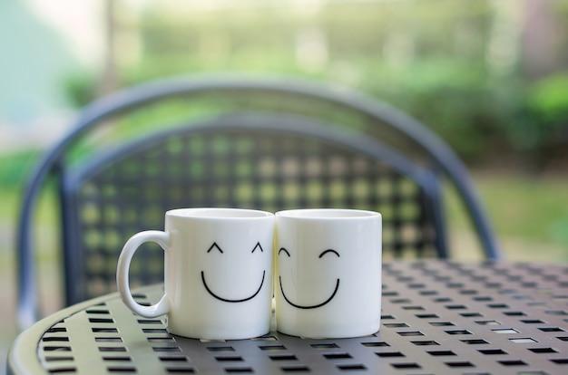 愛のコンセプトについて、木のテーブルの上に2つの幸せなカップ Premium写真