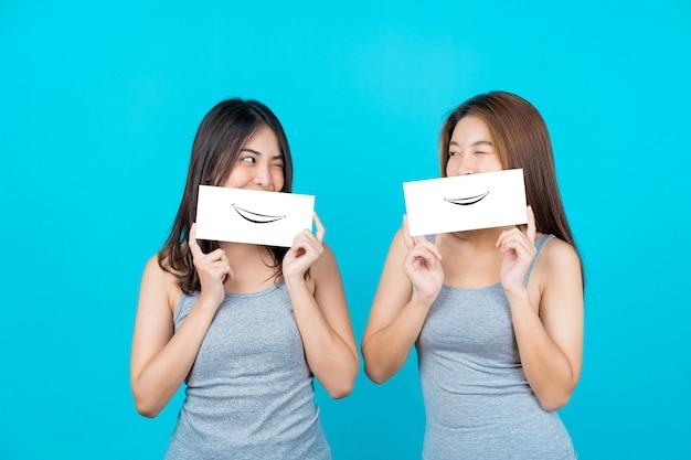 2 азиатских усмехаясь молодой женщины показывая и представляя с плакатами на изолированной стене голубого цвета Premium Фотографии