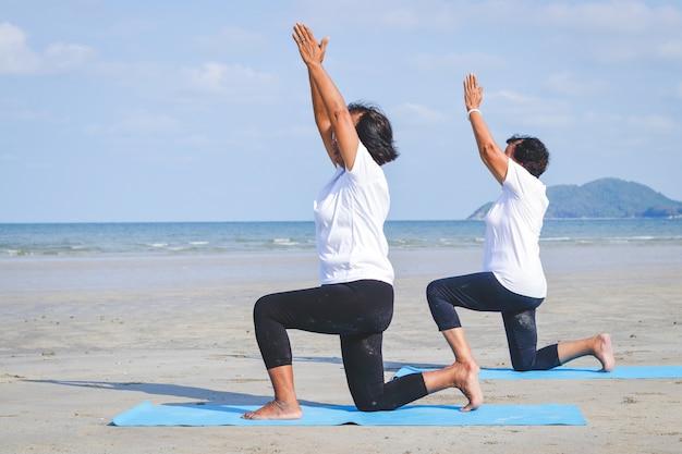 砂の上に座って、海でヨガをしている2人のアジアの高齢女性 Premium写真