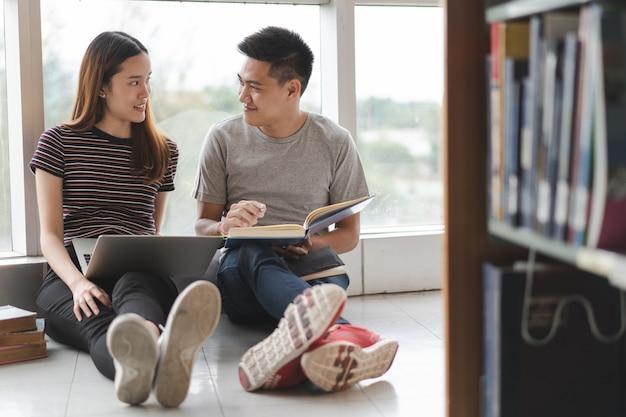 アジアの2人の学生が図書館でプロジェクトを研究しています。 Premium写真