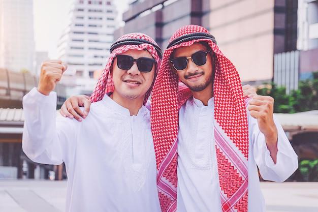 市内で両手を上げることによって立っている2人のアラブのビジネスマン Premium写真