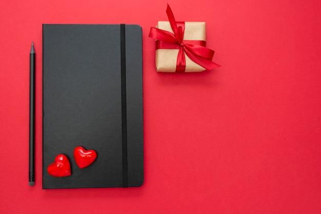 赤い背景の2つの心とギフトボックスに黒のノートブック。バレンタインデーのコンセプト。 Premium写真