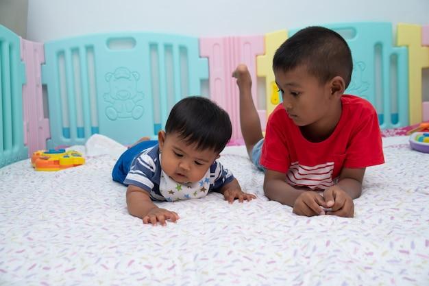 部屋で遊ぶかわいい2つの小さな男の子 Premium写真