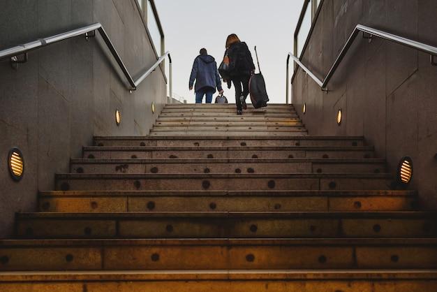 はしごを登る彼らのスーツケーストロリーを持つ2人の乗客のシルエット Premium写真