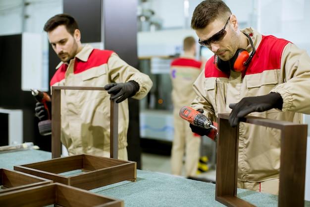 工場で家具を組み立てる2人の若い労働者 Premium写真