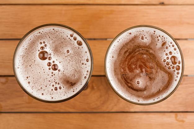 トップビューの木製の背景にガラスの上の泡とビールの2つのマグカップ Premium写真