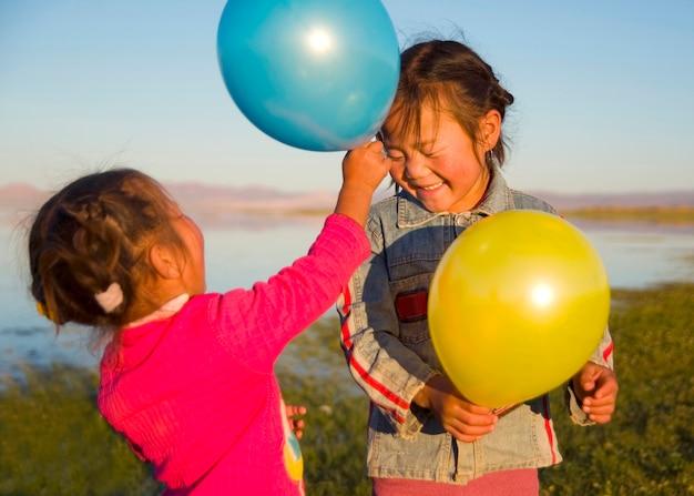風船でお互いに遊んでいる2人の少女。 無料写真