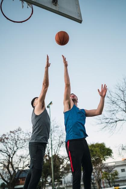 バスケットボールをする2人の若い友人 Premium写真