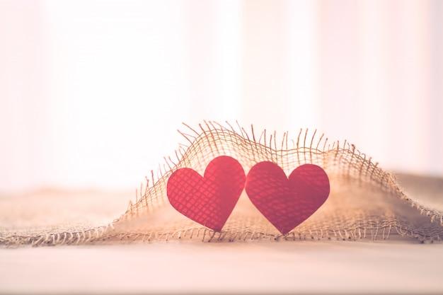 バレンタインデーの袋布で2つの赤いハート Premium写真