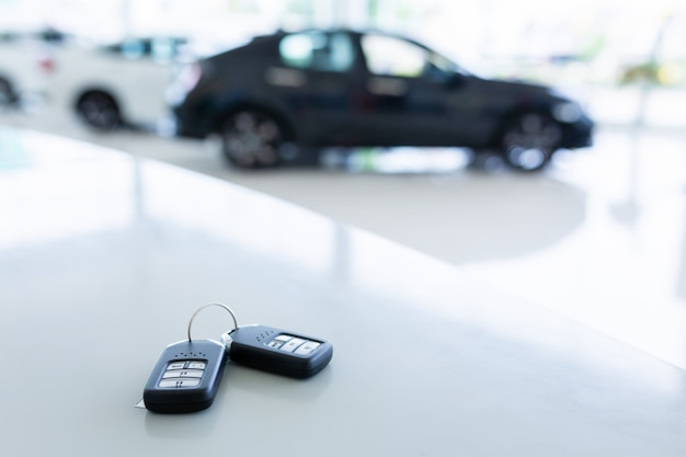 新しい自動車ショールームの作業テーブルに置かれた2つの新しいリモートキーを備えた自動車ショールームの新しいキー。 Premium写真