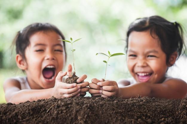 一緒に黒い土に若い木を植えている2つのかわいいアジアの子供の女の子 Premium写真