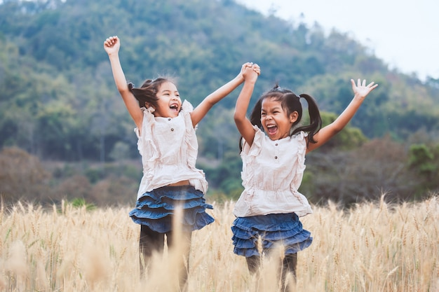 麦畑で一緒に遊んでジャンプを楽しんで2人の幸せなアジアの子女の子 Premium写真