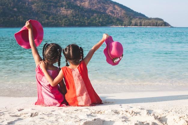 2 милых азиатских девушки маленького ребенка держа шляпу сидя и играя совместно на пляже Premium Фотографии