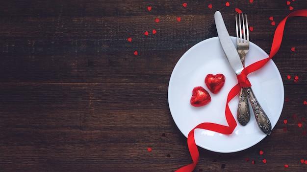 バレンタインデーのお祝いテーブルセッティング、フラット2つの赤いハート形のチョコレート菓子 Premium写真
