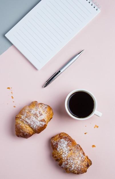 クロワッサンと2色の背景上の事業計画とデザインのアイデアのためのノートとコーヒー・マグ Premium写真