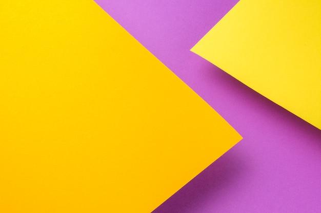 紫色の背景の上に黄色とオレンジ色の紙が2枚飛び出します。シートは影を投げる。 Premium写真